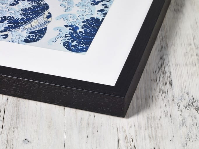 A corner of a high quality framed image made from wood painted black